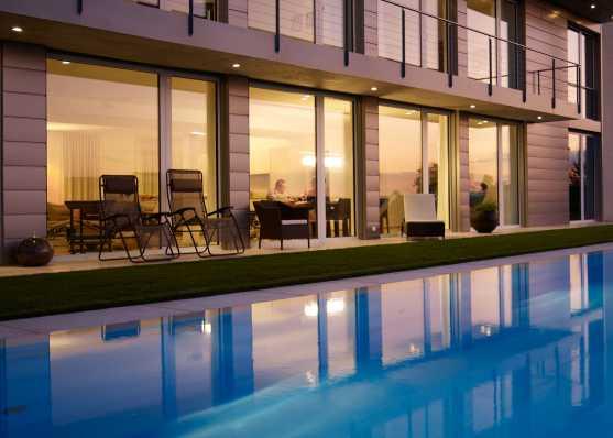 Luxus Gartenschwimmbad mit Überlaufrinne und Folienauskleidung vor Villa