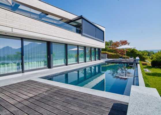 Schwimmbad mit Naturstein-Auskleidung vor Villa