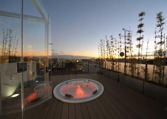 Whirlpool mit Überlaufrinne auf Attika-Terrasse bei Sonnenuntergang