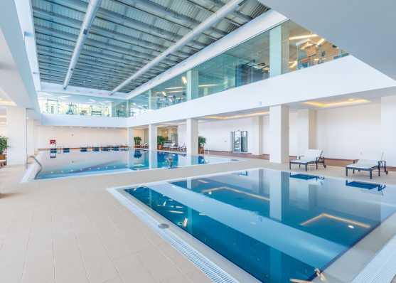 Weitläufiges Indoor-Swimmingpool mit Fitnessbereich im oberen Stockwerk