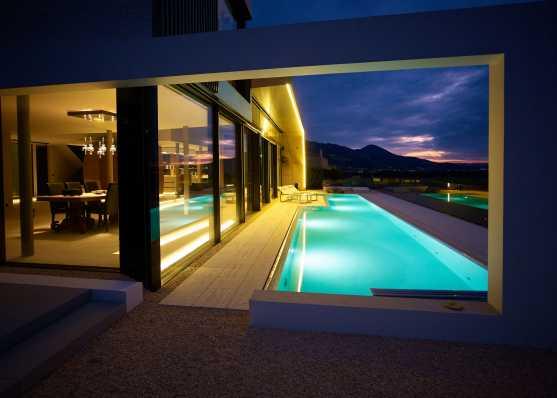 Villa mit Schwimmbad in Abenddämmerung
