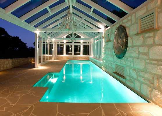 Swimmingpool mit Überdachung beleuchtet in edlem Ambiente