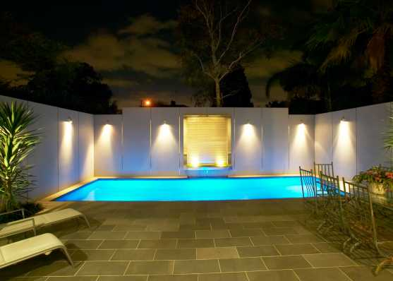 Swimmingpool beleuchtet mit Wasserfall