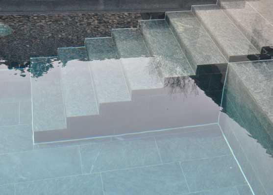 harmonisch eingebaute Schwimmbadtreppe Typ Milano mit Granitplatten ausgekleidet