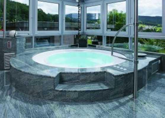 Whirlpool indoor mit Steinplatten umrandet