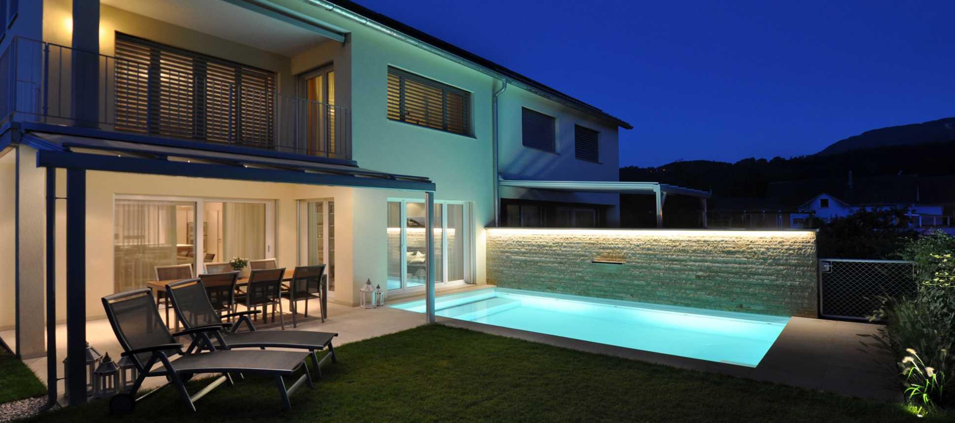 Haus mit Swimmingpool beleuchtet